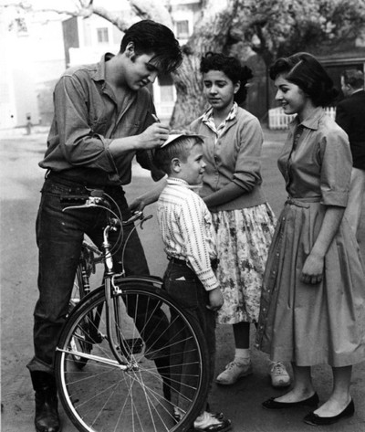 Young Elvis Presley, out for a bike ride and signing autographs