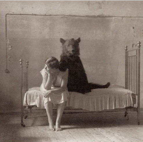 Woman sitting on a bed with a bear
