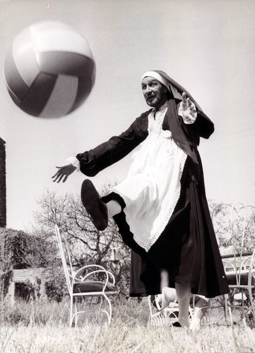 Vincent Price, dressed as a nun, kicking a beach ball