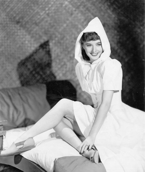Barbara Stanwyck, showing a little leg and wearing a hoodie
