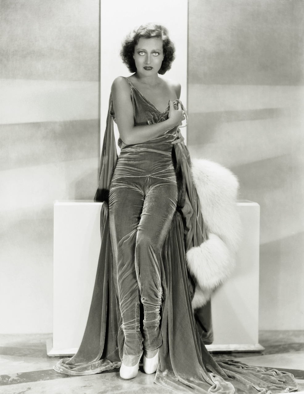 Joan Crawford in a spaghetti strapped velour pantsuit-dress with atrain