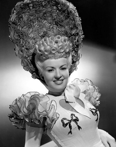 Betty Grable (I think) with curls, bonnet, and ruffles