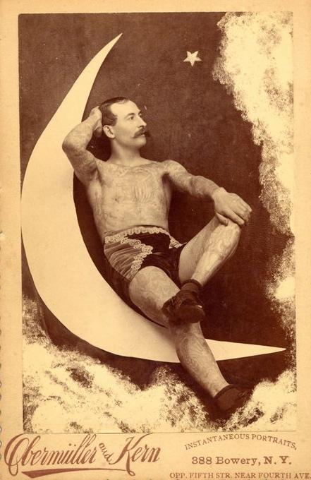 Tattooed, mustachioed man on a papermoon