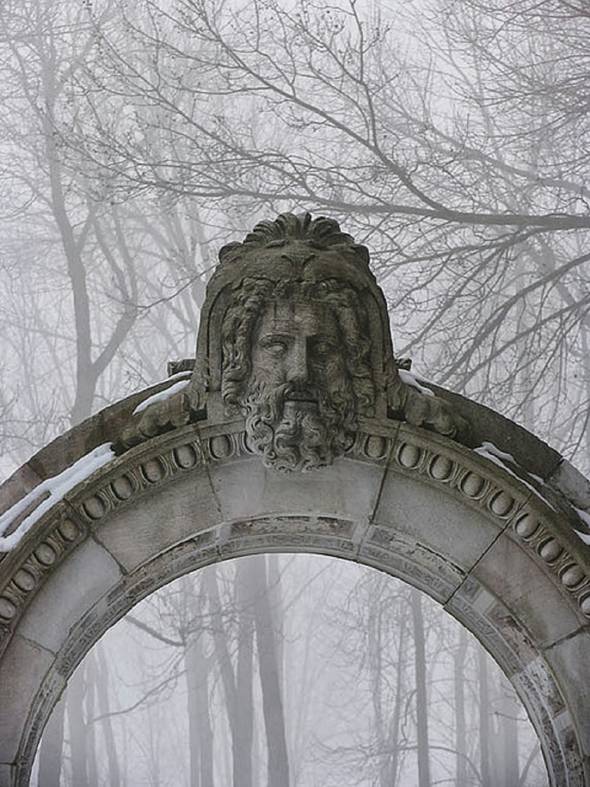 Stone arch in a foggy forest