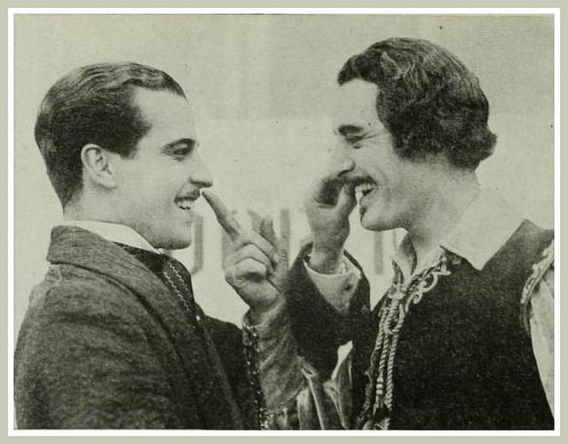 Ramon Novarro and John Gilbert, touching each other'smoustaches