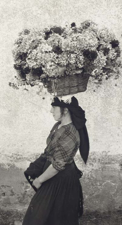 Balancing a basket of flowers on her head
