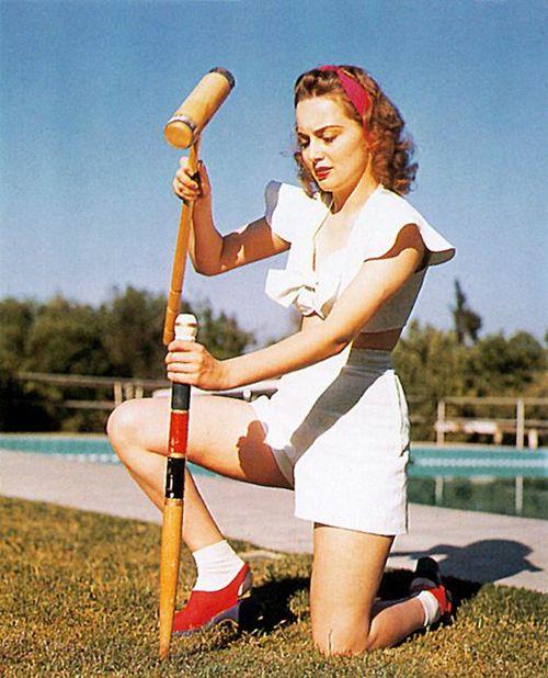 Young Olivia DeHaviland setting up a croquetgame