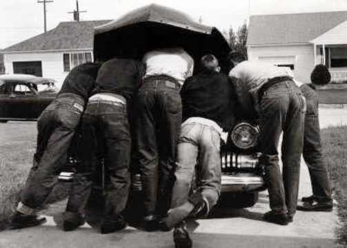Six men working on a car, late 1940s