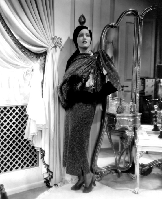 1934: Gloria Swanson (1897 - 1983) models one of the many gowns, designed and created by Rume Hubert for her role in the film 'Music In The Air', directed by Joe May for Fox.