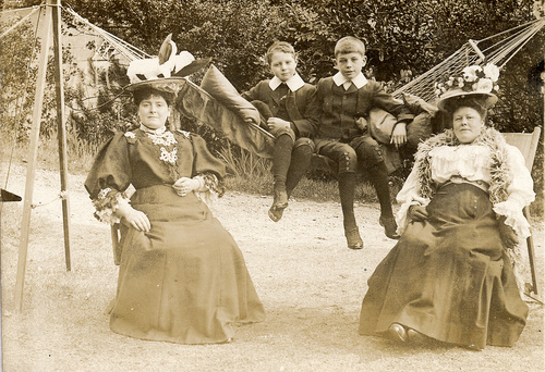 Mothers in their garden finery with their children in a hammock