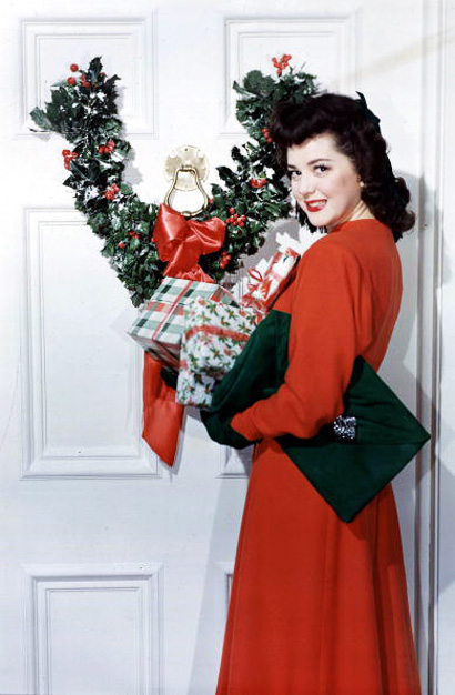 1953. A picture of American film actress Ann Rutherford, standing with Christmas presents next to a door decorated with a holly wreath.