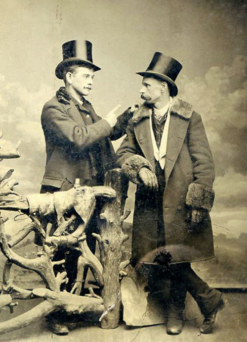Men together, with top hats andstache