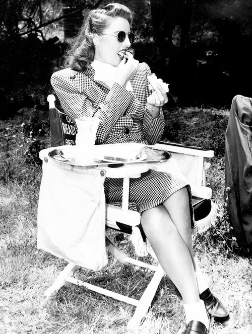 Barbara Stanwyck having a nosh on the set