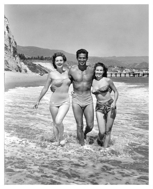 Actor George Nader with a couple of bathing beauties