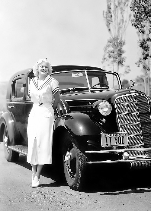 Jean Harlow poses with her Cadillac limousine, 1934