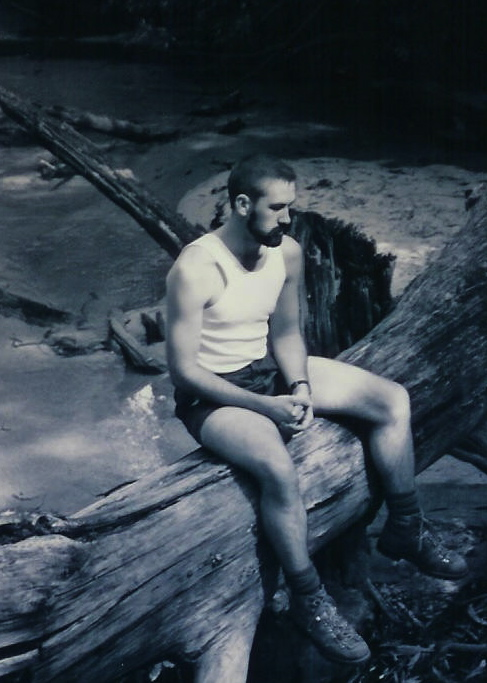 Bearded man sitting by acreek