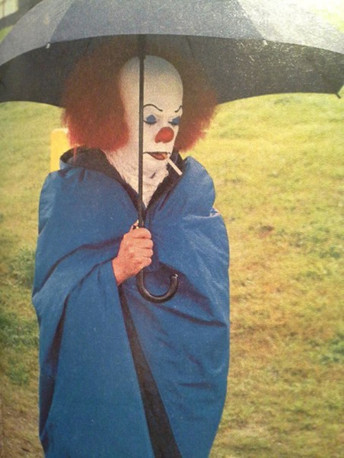 "Tim Curry (as the evil clown 'Pennywise') taking a smoke break in the rain during the filming of Stephen King's ""It"""