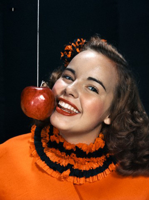 01 Jan 1940 --- 1940s 1950s smiling young woman wearing halloween costume bobbing for apple on a string --- Image by © Camerique/ClassicStock/Corbis