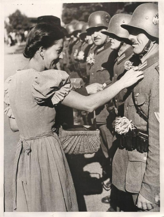 a-local-girl-pinning-a-flower-on-a-german-soldiers-uniform-in-olbersdorf-as-nazi-forces-occupy-the-sudetenland-1938