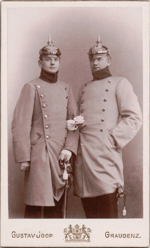 Prussian soldiers arm in arm with a flower in hand and pickelhaubes on their heads
