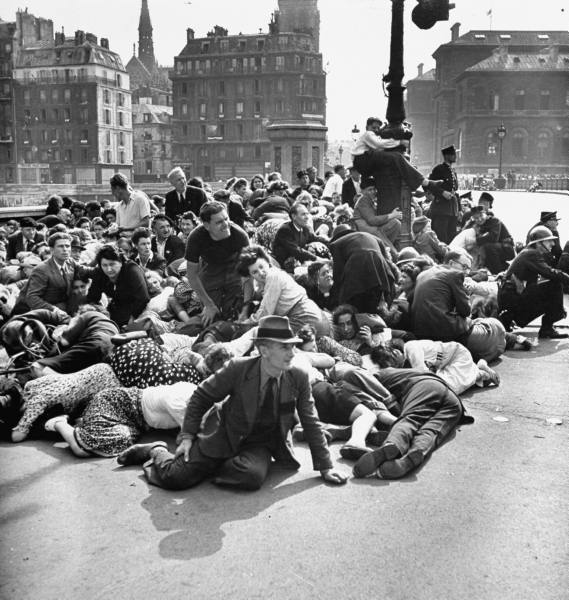Group of Parisiens take cover in the street from a leftover German sniper after liberation, 1945