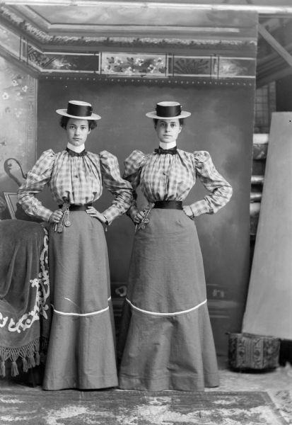 Two women together, identical outfits (early vaudeville?)