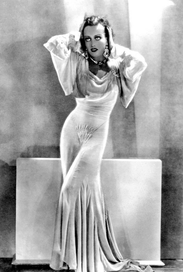 """Joan Crawford wearing a gown by Adrian in a publicity photo for """"Our Blushing Brides"""",1930"""