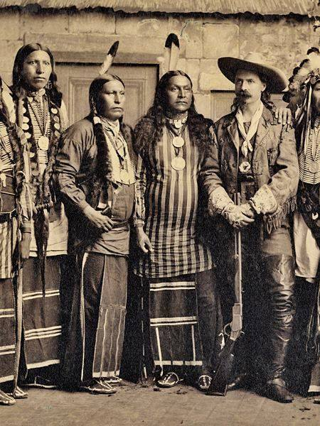 "Buffalo Bill (in thigh high leather boots) and some Native Americans, perhaps from in one of his ""Wild West"" shows"