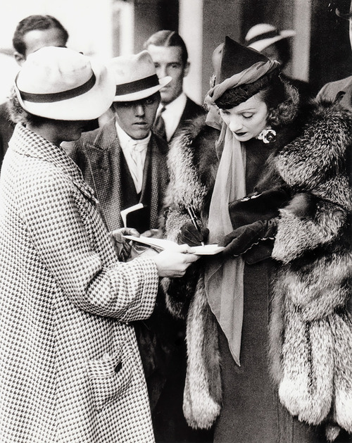 Marlene Dietrich signing autographs, wearing a silver foxcoat