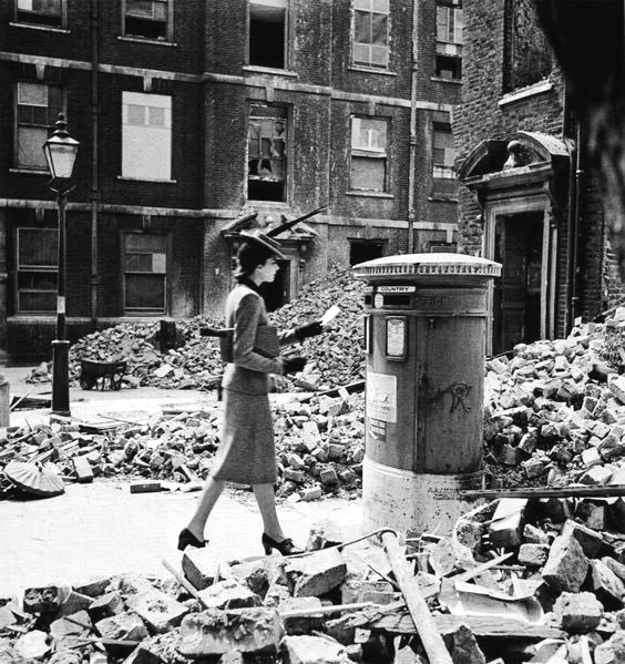Woman posting a letter in a debris strewn street during the Blitz (Nazi bombing) of London, 1940