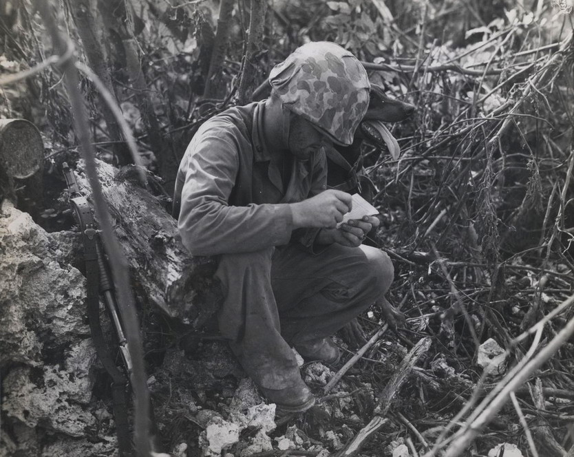 US soldier reading message brought by delivery dog, Vietnam War, 1960s