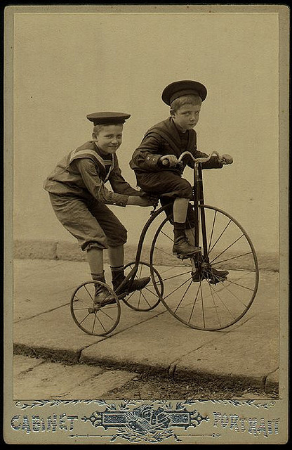 Children riding an old fashionedtricycle