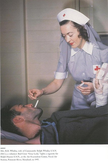 Red Cross volunteer lighting a cigarette for an injured sailor,WWII