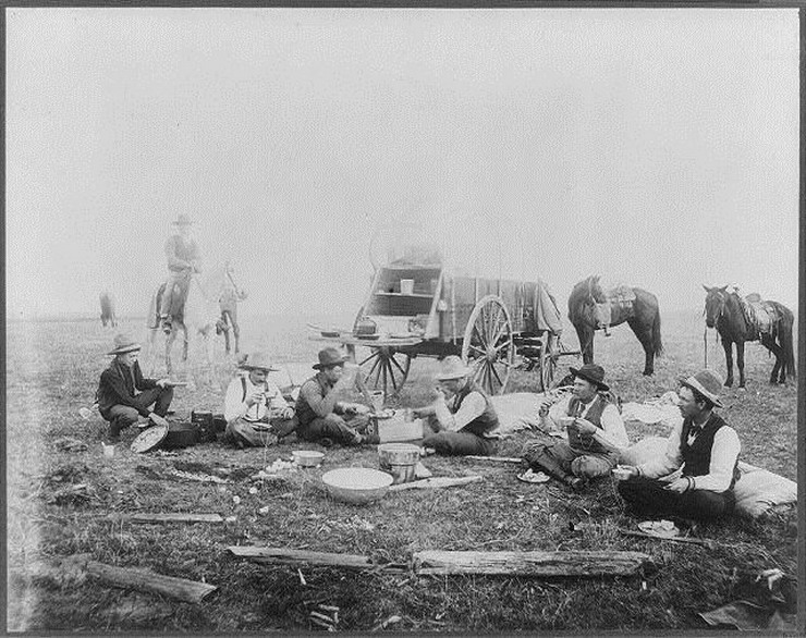 Authentic cowboys having breakfast by the chuck wagon, 1800s