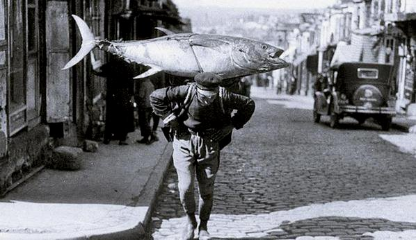 Fisherman carrying a large tuna on his back through the streets of Istanbul, Turkey, 1930s