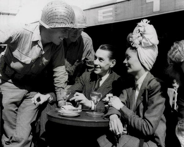 American soldiers laughing with a French couple in a cafe after the liberation of Paris,1944