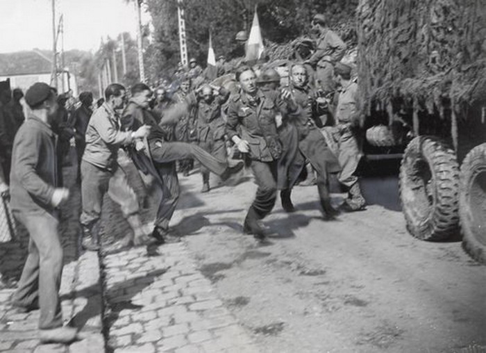 French citizens kicking captured Nazi German soldiers near the end of WWII, 1944