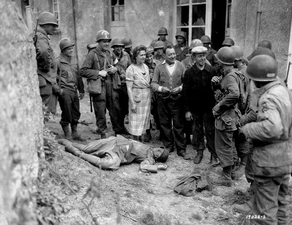Happy French citizens and American soldiers gathered around the body of a dead Nazi soldier after the D-Day invasion, 1944