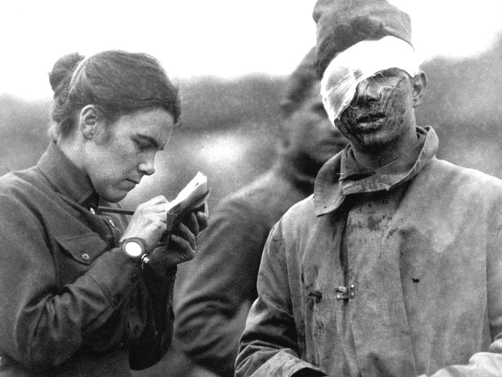 Woman writing down a letter from a wounded soldier, WWI