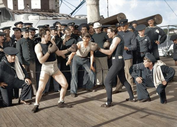 Colourized photo of marines or sailors having a boxing match on the deck of a ship, circa 1905