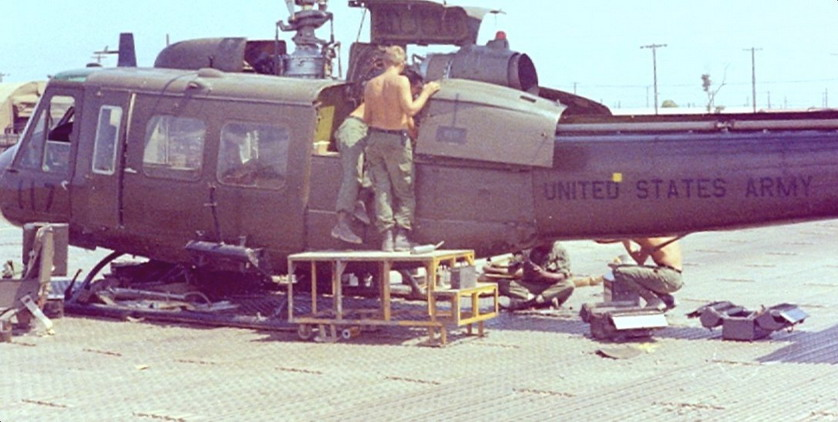 Shirtless American soldiers repairing a helicopter, Vietnam War, 1960s