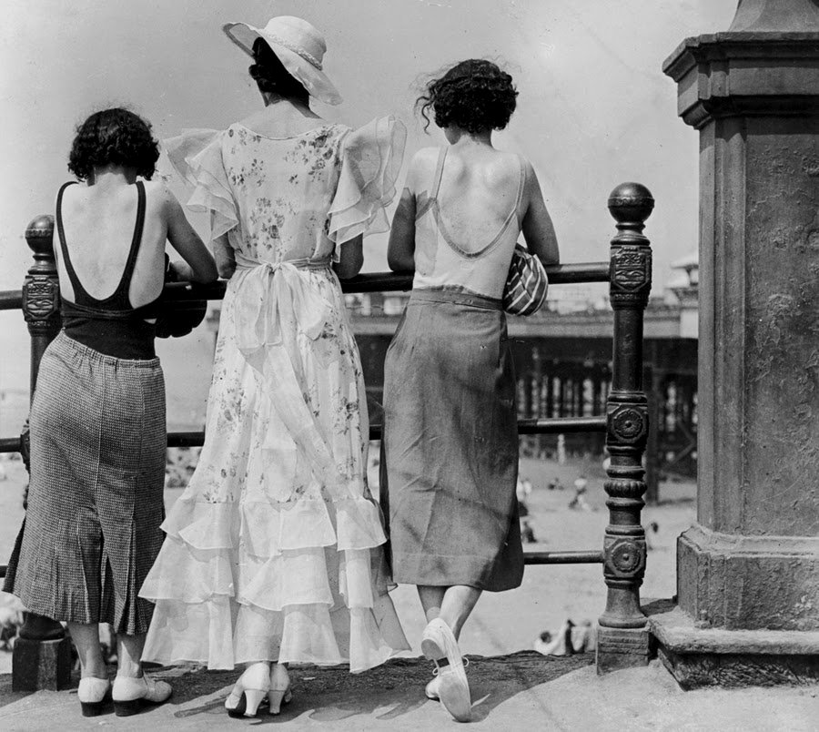 Three women looking down at the beach from the boardwalk, 1920s