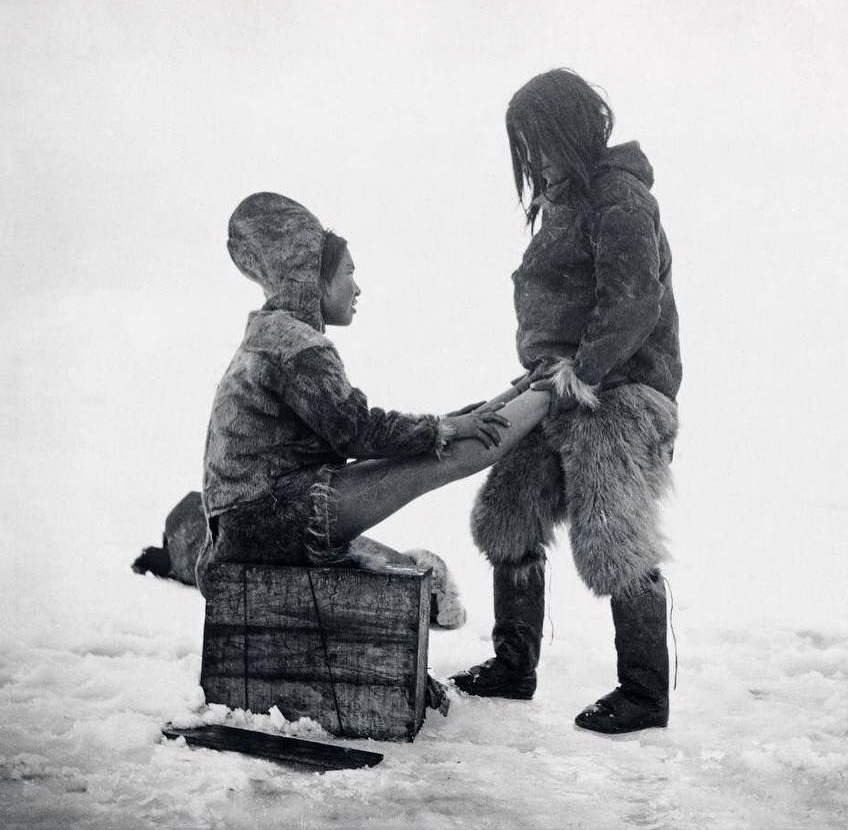 Inuit man warms his wife's feet, somewhere in the Arctic, 1890s
