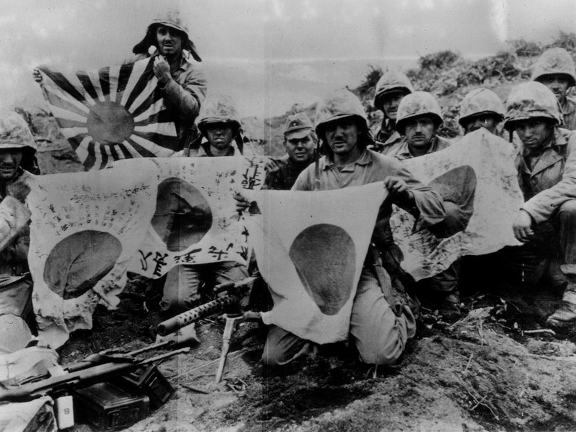 American soldiers hold up captured Japanese battle flags, Pacific, WWII