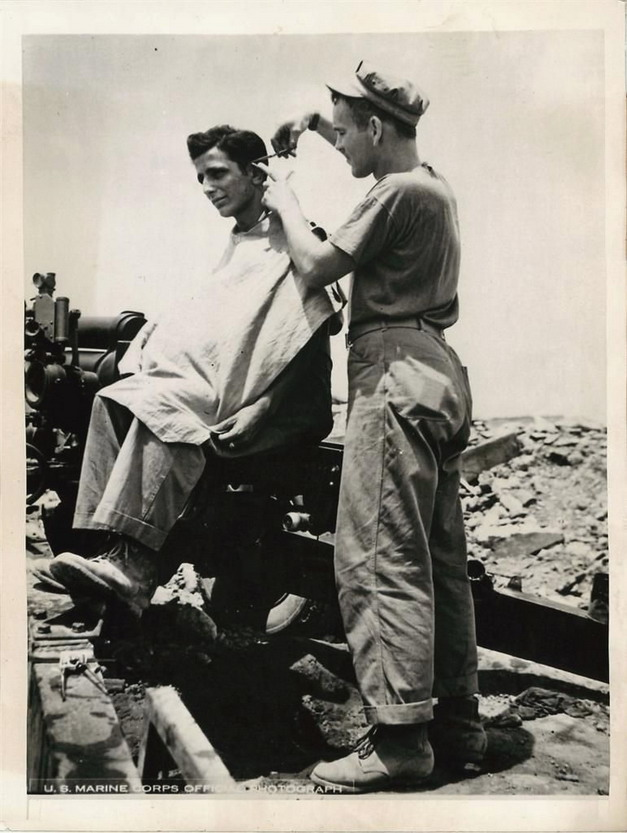 Soldier getting a haircut on Okinawa after US forces took the island, WWII (1944?)