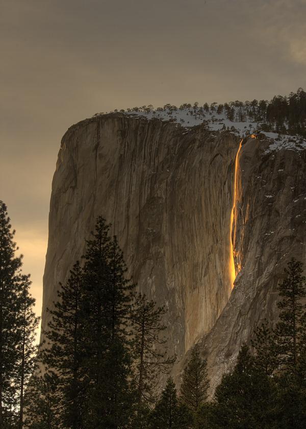 Setting sun hitting a waterfall so it looks like lava, Yosemite,California