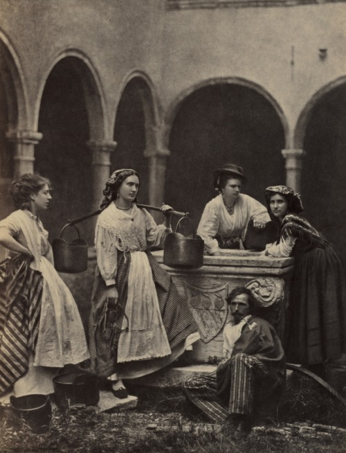 Four women and a man around a courtyard well
