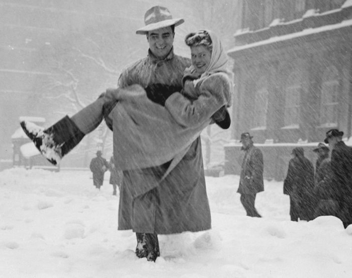 Man carrying a women in a snowstorm, NYC, by Art Whittaker, 1947