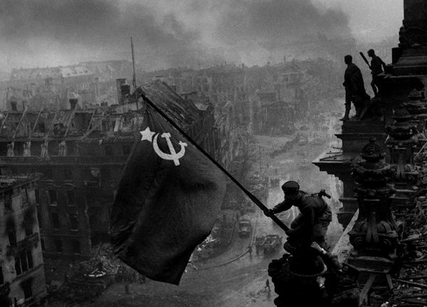 Soviet flag flying over a destroyed Berlin at the end of WWII, 1945