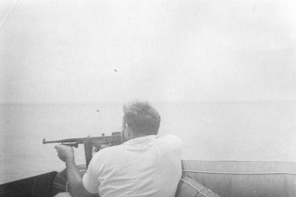 Ernest Hemingway firing a gun off his yacht off the coast of Florida,1930s